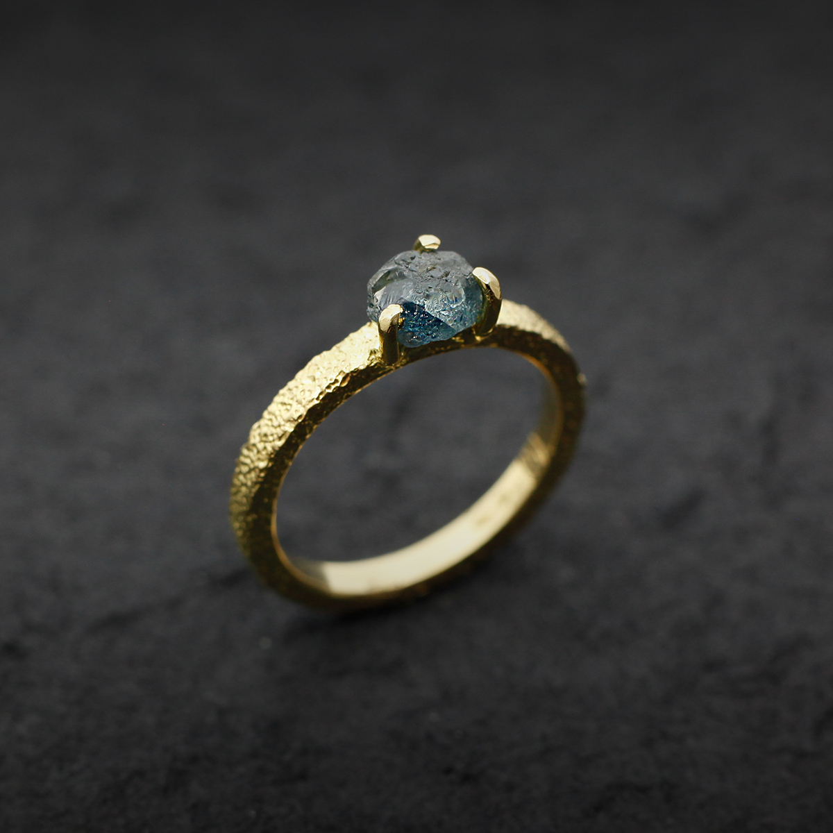 Yellow gold engagement ring with a rough sapphire in a solitaire.